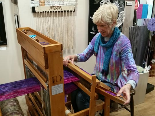 Barbara Decker demonstrating her prowess on a loom at Cazenovia Artisans