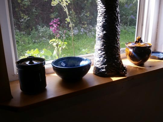 Ceramic pieces by Shawn McGuire glowing in a sunny window