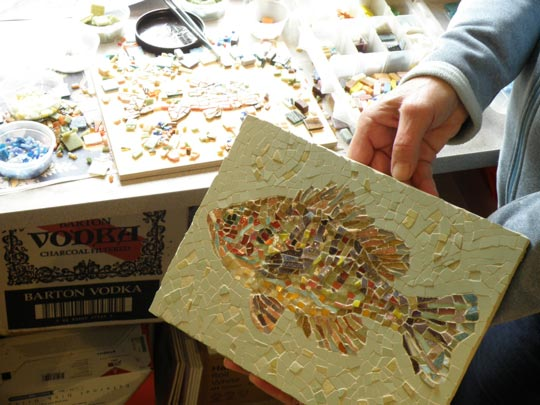 Mary Padgett shows her recent fish tile piece